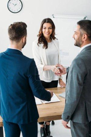 Photo pour Mise au point sélective de séduisante et souriant, conseiller et investisseur se serrant la main au milieu de travail - image libre de droit