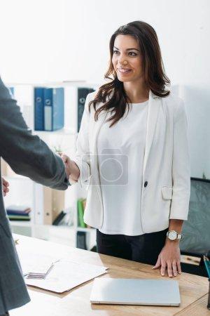Photo pour Séduisante et souriante conseiller et investisseur se serrant la main au milieu de travail - image libre de droit