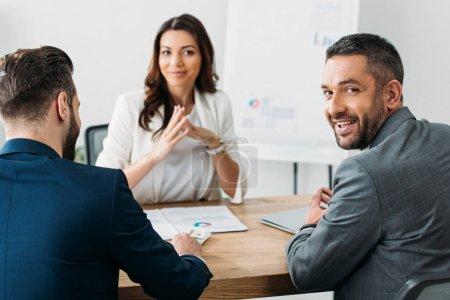 Photo pour Mise au point sélective des investisseurs dans les costumes de parler avec un conseiller attrayant à l'espace de travail - image libre de droit