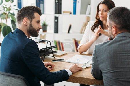 Photo pour Mise au point sélective des investisseurs beau en costume, parler avec un conseiller attrayant à l'espace de travail - image libre de droit