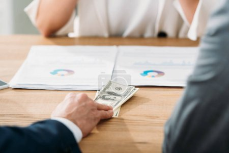 Photo pour Mise au point sélective d'homme détenant des billets de dollar avec femme sur fond - image libre de droit