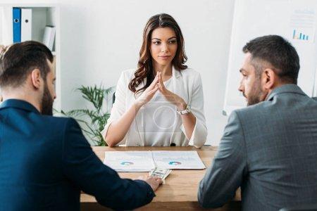 Photo pour Mise au point sélective de conseiller attrayant et investisseurs en costume à l'espace de travail - image libre de droit