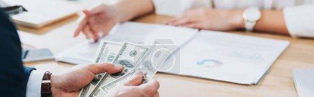 Photo pour Mise au point sélective d'homme détenant des billets de dollar au bureau - image libre de droit