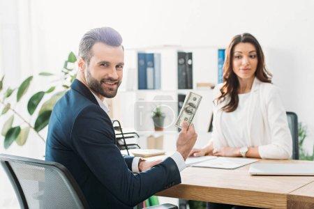 Photo pour Mise au point sélective des investisseurs détenant des billets de dollar et conseiller en regardant - image libre de droit