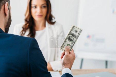 Photo pour Mise au point sélective d'investisseur en costume détenant des billets de dollar avec conseiller sur fond - image libre de droit