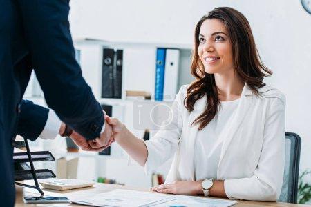 Photo pour Belle et souriante conseiller et investisseur en costumes se serrant la main au milieu de travail - image libre de droit