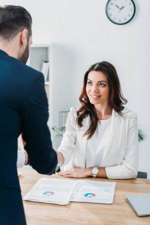 Photo pour Mise au point sélective de beau conseiller en serrant la main de l'investisseur sur lieu de travail - image libre de droit