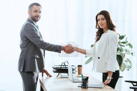 Photo pour Belle conseiller et investisseur beau en costume, se serrant la main au milieu de travail - image libre de droit