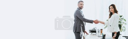 Photo pour Belle conseiller et investisseur en costumes se serrant la main au milieu de travail - image libre de droit