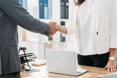 Photo for Partial view of woman and man shaking hands at office - Royalty Free Image