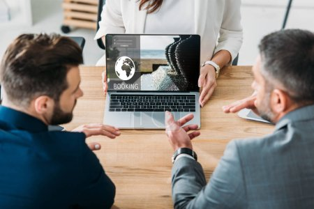 Photo for Selective focus of advisor showing to investors laptop with booking website on screen at workplace - Royalty Free Image