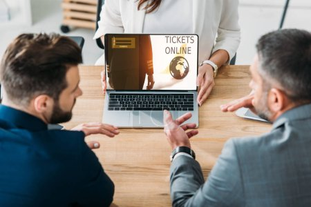 Photo for Selective focus of advisor showing to investors laptop with tickets online website on screen - Royalty Free Image