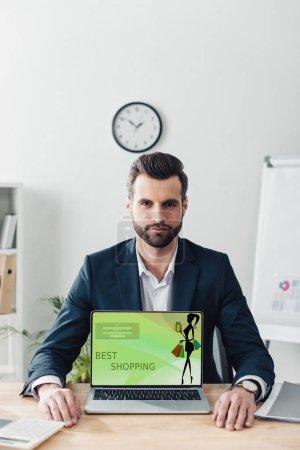 Photo pour Conseiller beau en costume, indiquant un ordinateur portable avec meilleur shopping site sur écran - image libre de droit