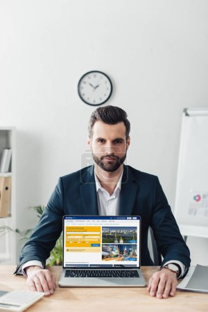 Photo for Handsome advisor in suit showing laptop with booking website on screen - Royalty Free Image
