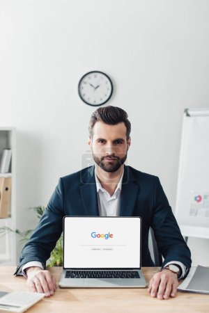 Photo pour Beau conseiller en costume montrant portable avec google site sur écran - image libre de droit