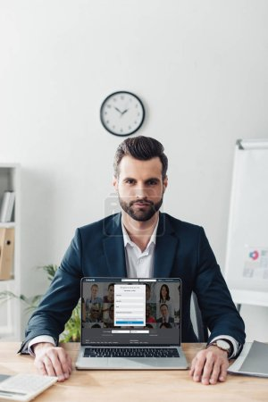 Photo for Handsome advisor in suit showing laptop with linkedin website on screen at office - Royalty Free Image