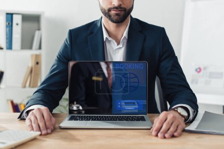 Photo for Cropped view of advisor in suit showing laptop with booking website on screen at office - Royalty Free Image