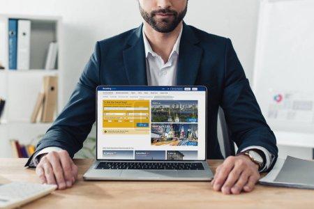Photo pour Vue partielle du conseiller en costume montrant ordinateur portable avec le site Web de réservations sur écran au bureau - image libre de droit