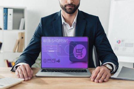 Photo pour Vue recadrée de conseiller en costume montrant portable avec site web-shopping sur écran au bureau - image libre de droit