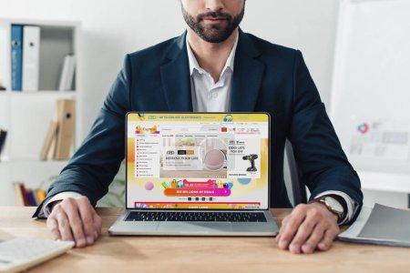 Photo pour Vue recadrée du conseiller en costume montrant l'ordinateur portable avec le site Web aliexpress à l'écran sur le lieu de travail - image libre de droit