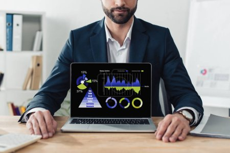 Photo for Cropped view of advisor in suit showing laptop with rate website on screen - Royalty Free Image