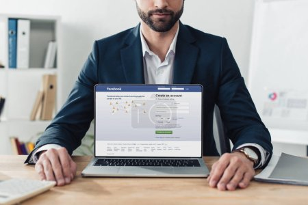 Photo pour Recadrée vue du conseiller en costume montrant ordinateur portable avec le site facebook sur écran - image libre de droit