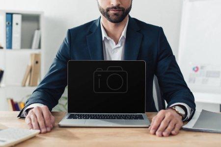 Photo pour Recadrée vue du conseiller en costume montrant portable avec espace copie - image libre de droit