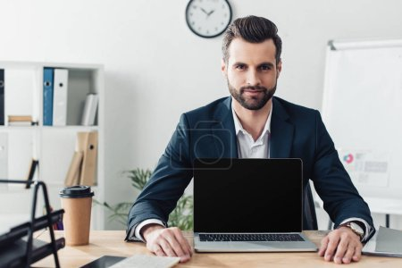 Photo for Handsome advisor in suit showing laptop with blank screen at office - Royalty Free Image
