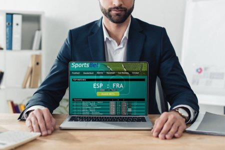 Photo for Cropped view of advisor in suit showing laptop with sportsbet website on screen at office - Royalty Free Image