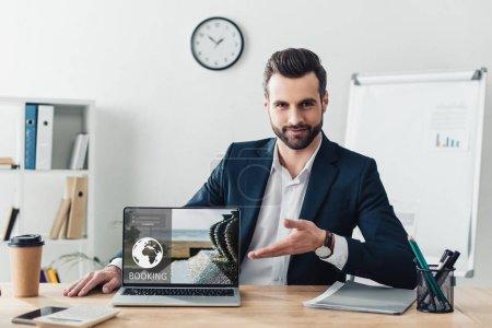 Photo pour Beau conseiller en costume pointant avec doigts à ordinateur portable avec le site de réservation à l'écran au bureau - image libre de droit
