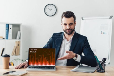 Photo for Handsome advisor in suit pointing with fingers at laptop with online trade website on screen at office - Royalty Free Image