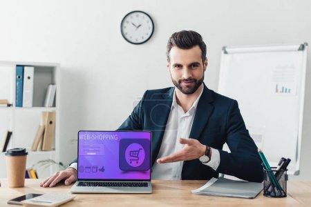 Photo pour Beau conseiller en costume pointant avec doigts à ordinateur portable avec site web-shopping sur écran - image libre de droit