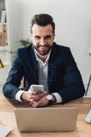 Photo pour Conseiller en souriant et beau en costume à l'aide de smartphone sur lieu de travail - image libre de droit