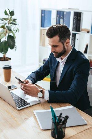 Photo pour Beau conseiller en costume à l'aide de smartphone avec ordinateur portable sur la table à l'espace de travail - image libre de droit