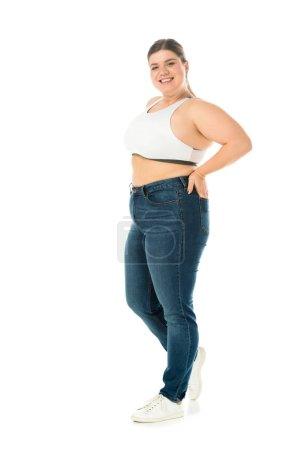 Foto de Feliz sonriente mujer con sobrepeso en jeans posando con la mano en el bolsillo aislado en blanco, el concepto de positividad de cuerpo - Imagen libre de derechos