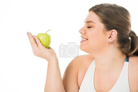Photo for Young smiling overweight woman looking at green apple isolated on white - Royalty Free Image