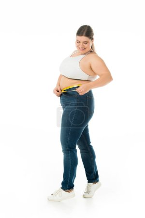 Photo for Smiling overweight woman in jeans measuring waist with measuring tape isolated on white, body positivity concept - Royalty Free Image