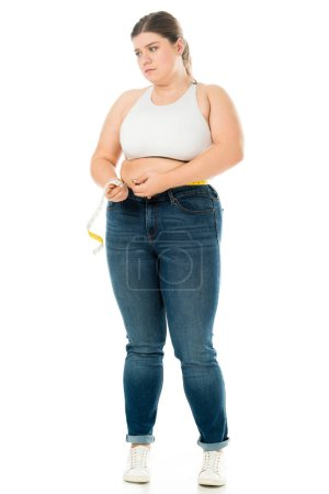 Photo for Dissatisfied overweight woman  in jeans measuring waist with measuring tape isolated on white, lose weight concept - Royalty Free Image