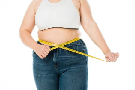 Photo for Cropped view of overweight woman  in jeans measuring waist with measuring tape isolated on white, lose weight concept - Royalty Free Image