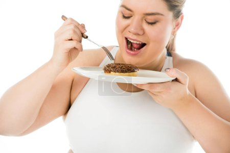 overweight woman eating sweet doughnut from plate isolated on white, body positivity concept