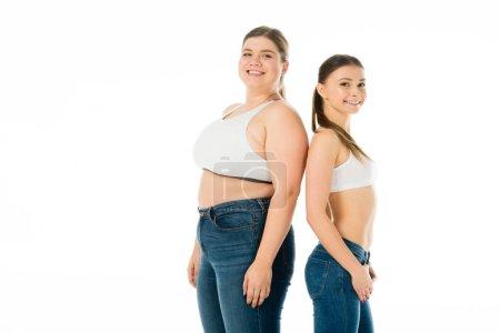 Foto de Sonriendo a las mujeres delgadas y con sobrepeso en Dril posando juntos aislado en concepto de positividad de cuerpo blanco, - Imagen libre de derechos
