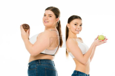 Photo for Happy slim and overweight women standing back to back together with doughnut and green apple isolated on white - Royalty Free Image