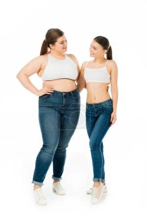 Foto de Mujeres delgadas y con sobrepeso felices abrazándose y mirándose aislados en blanco, concepto de positividad corporal - Imagen libre de derechos