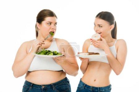 Photo pour Femme mince manger des beignets et femme en surpoids manger des feuilles d'épinards verts tout en se regardant isolé sur blanc - image libre de droit