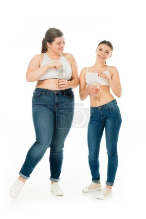 Photo for Happy slim and overweight women in jeans holding bottles with water isolated on white - Royalty Free Image