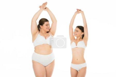 Foto de Jóvenes mujeres delgadas y con sobrepeso en ropa interior posando juntos aislados en blanco, concepto de positividad corporal - Imagen libre de derechos