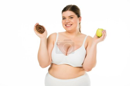 Photo for Cheerful young overweight woman holding doughnut and green apple isolated on white - Royalty Free Image