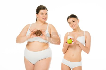 Photo for Young slim woman holding green apple while overweight woman holding sweet doughnut isolated on white - Royalty Free Image