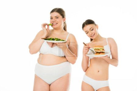 Photo for Slim woman in underwear looking at burger while overweight woman eating green spinach leaves isolated on white - Royalty Free Image