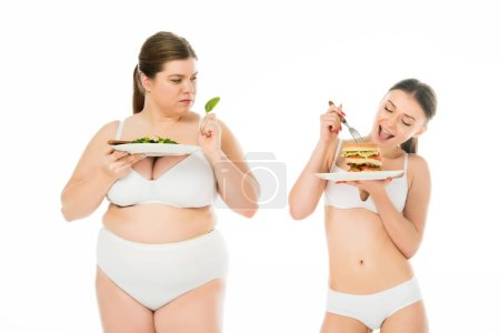 Photo for Slim woman in underwear eating burger while overweight upset woman holding green spinach leaf isolated on white - Royalty Free Image